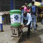 A man washes his hands as a preventive measure against the Ebola virus on a street in Monrovia